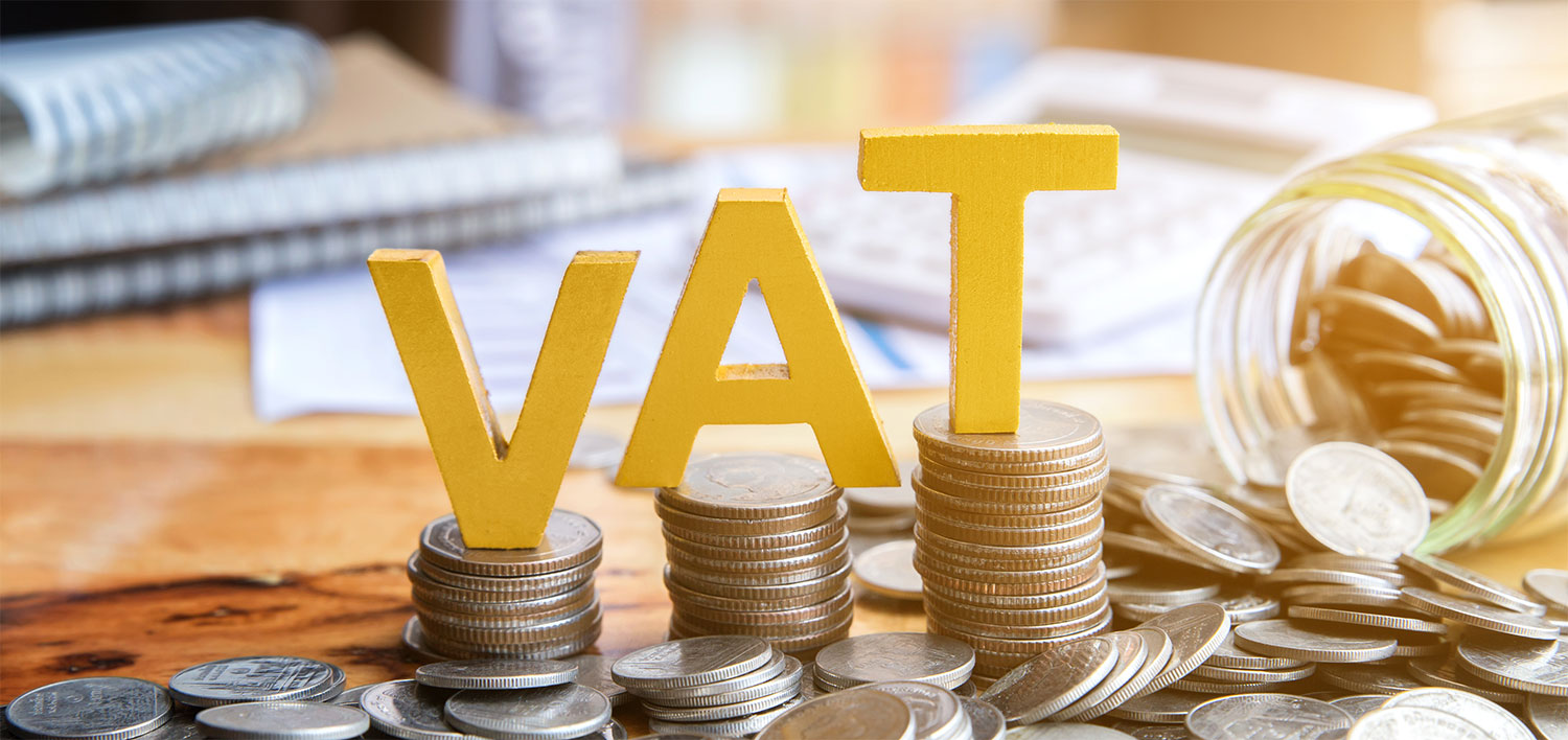 VAT sign sitting on top of coins piled up on a desk